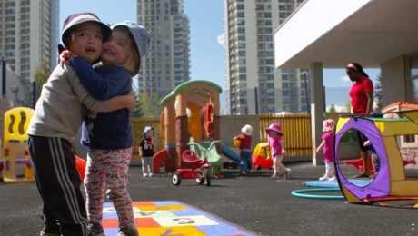 Two children smiling and hugging while standing on top of a hopscotch board at a day care facility.