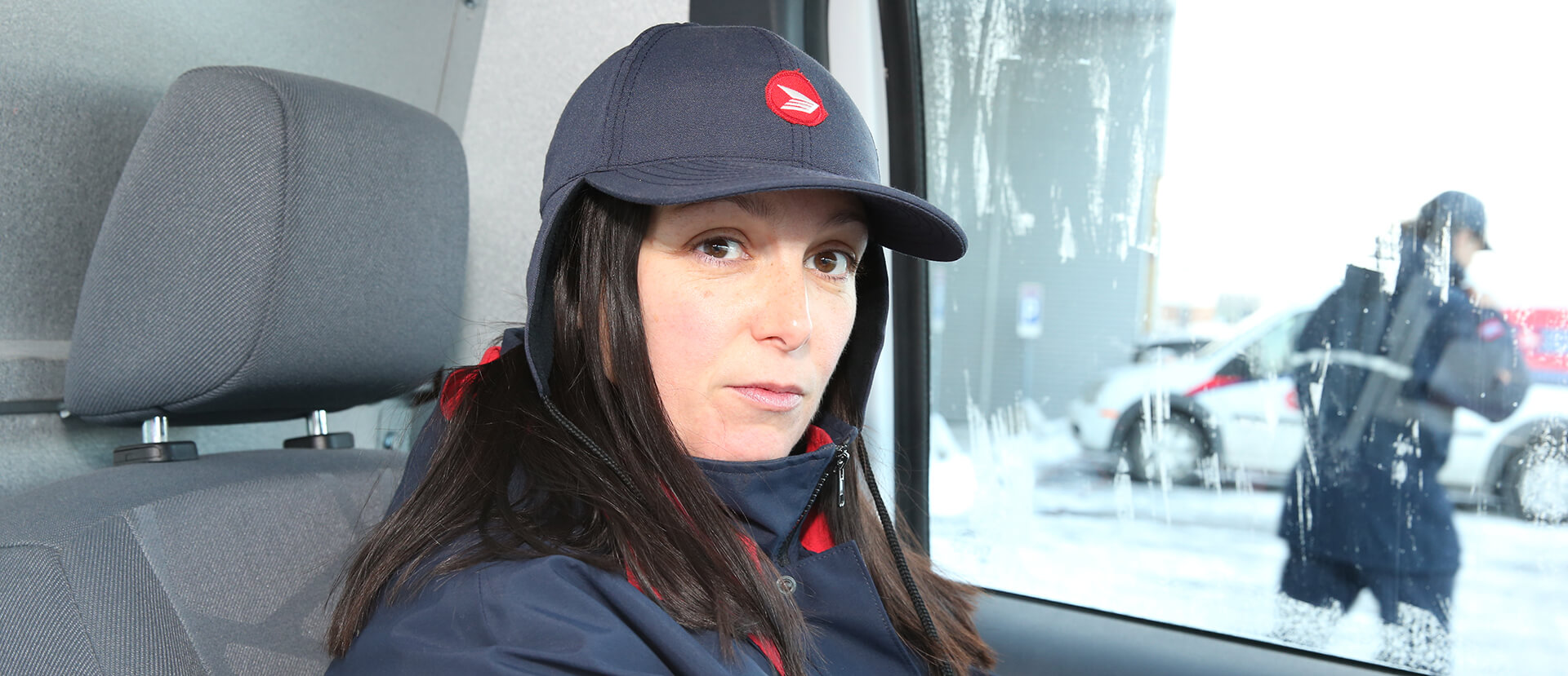Female postal worker sitting inside of a postal truck, staring directly into the camera with a serious look on her face.